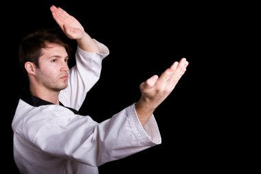 Young man practicing martial arts against black background