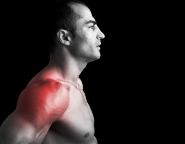 Muscular man suffering with shoulder pain on black background