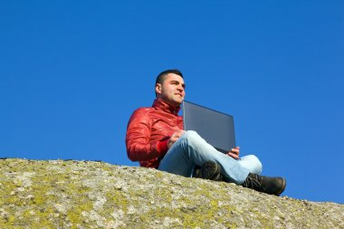 youn man with laptop outdoors against blue sky