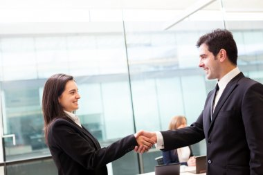 Business handshake at modern office with bussiness on bac
