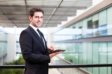 Happy smiling young businessman using his digital tablet at the