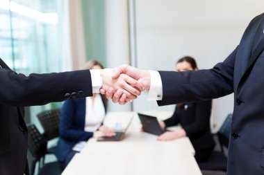 Business shaking hands in the office, finishing a meeting