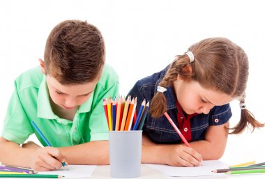 Two children drawing with colorful crayons, isolated over white
