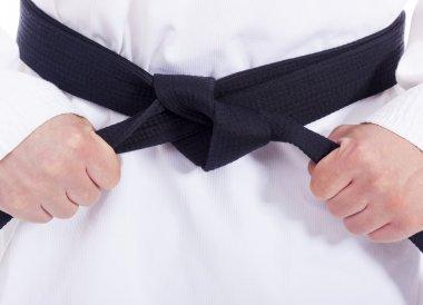 Closeup of a martial arts man tying his black belt