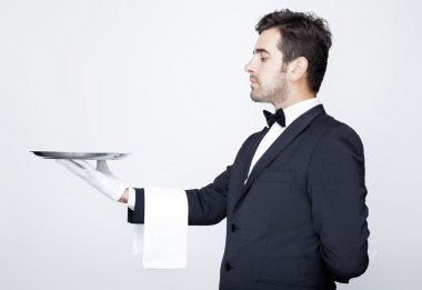 Professional waiter holding empty silver tray