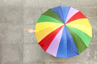 Woman hidden under multicolored umbrella and checking if it's ra