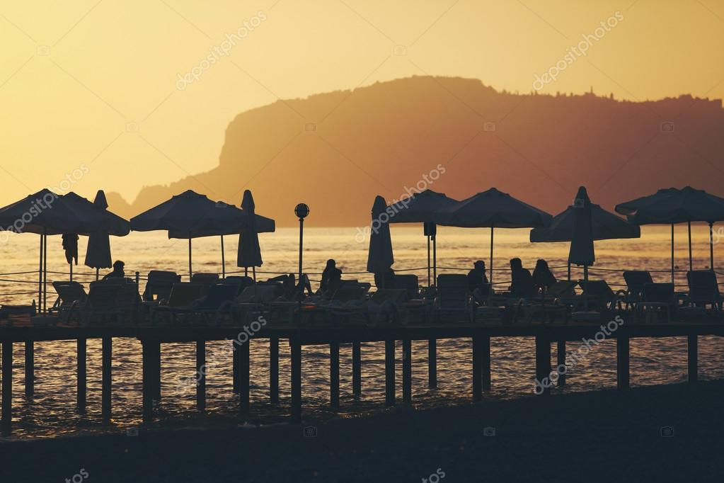 Silhouette of chairs and umbrellas on deck. Summer resort
