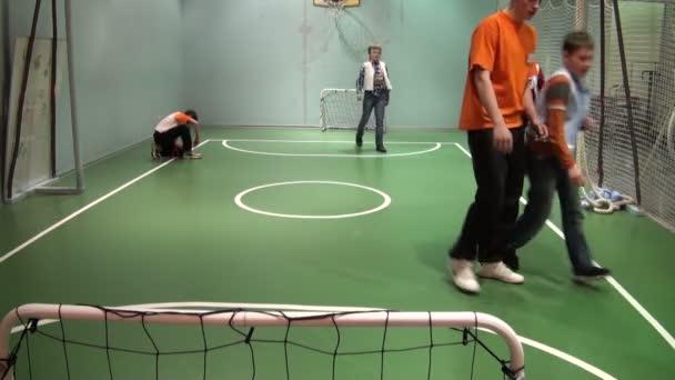 děti hrají fotbal v tělocvičně