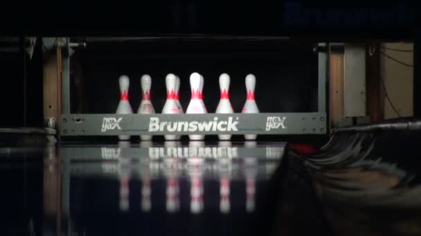 míč rolích a porazí kuželky na bowling lane, svítí ve tmě