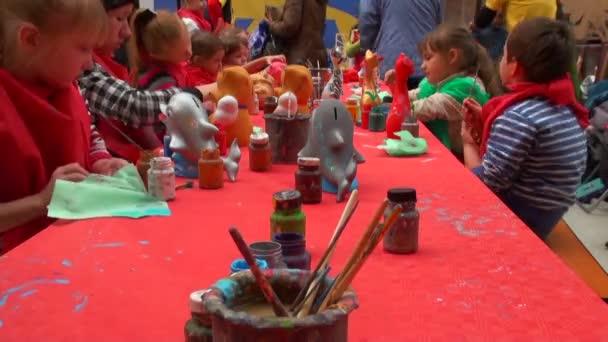 Kinderen zitten rond bureau genieten van schilderen met kleuren in