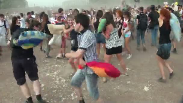 A crowd of people fighting pillows
