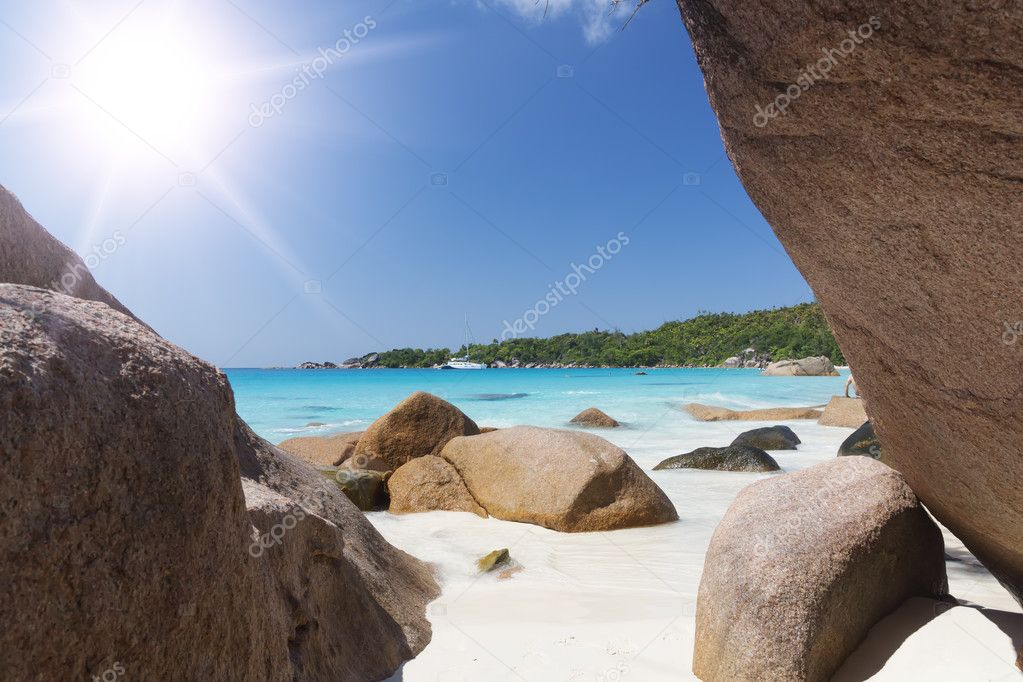 White coral beach sand and azure indian ocean. Sailing yacht on