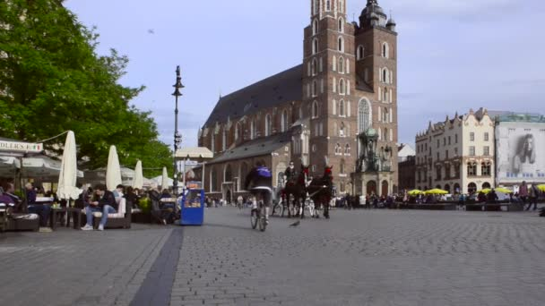 Horse drawn carriages with guides in front of the St. Marys Basilica in Krakow, Poland