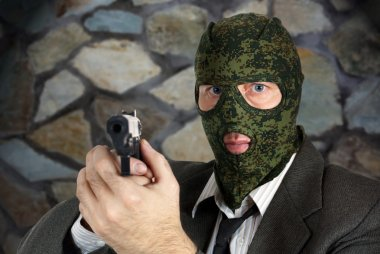 Killer in camouflage mask is aiming with a pistol