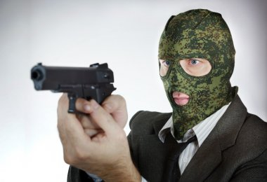 Man in camouflage mask with a pistol