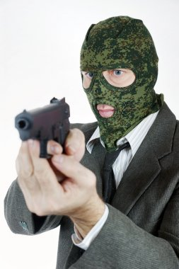 Killer in camouflage mask with a pistol