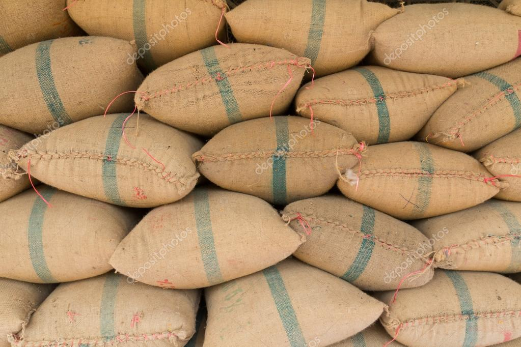 Old hemp sacks containing rice placed profoundly stacked