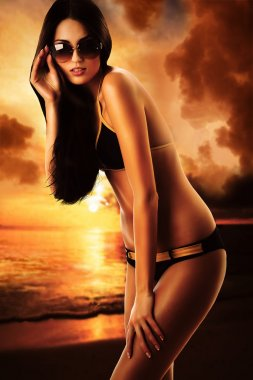 woman in swimsuit with hand on sunglasses at sunset