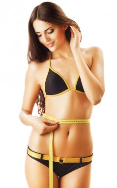 smiling beautiful woman in swimsuit looking at measure