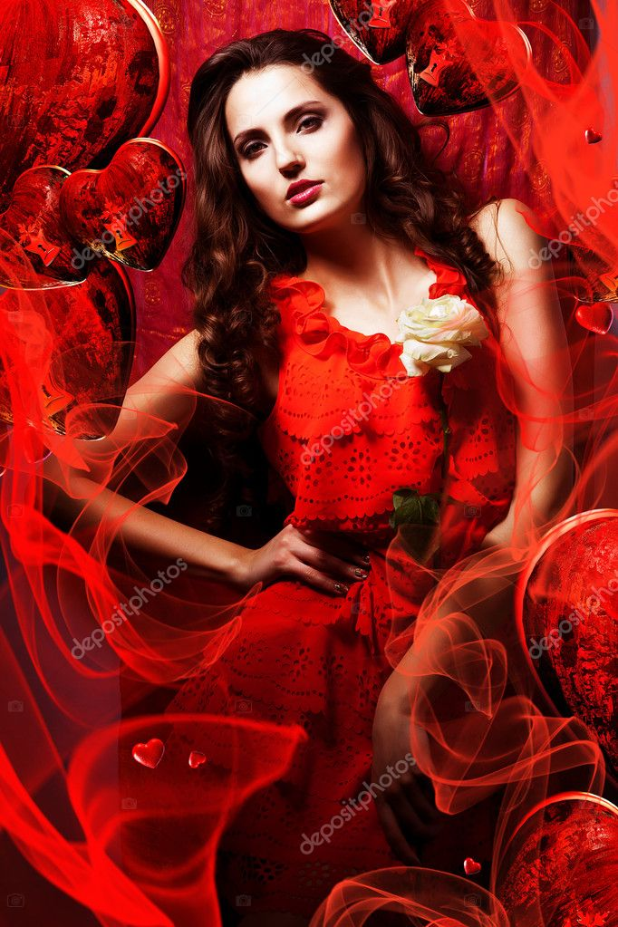 beautiful hot woman in love in red dress around fabric and heart