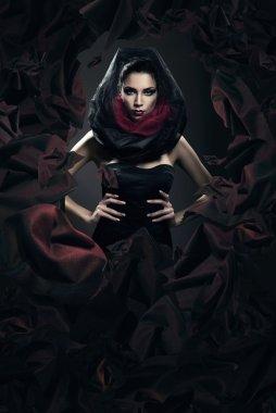 Mysterious woman in black hood in dark fabric