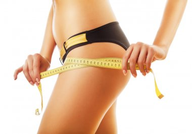 slimming woman measuring her body