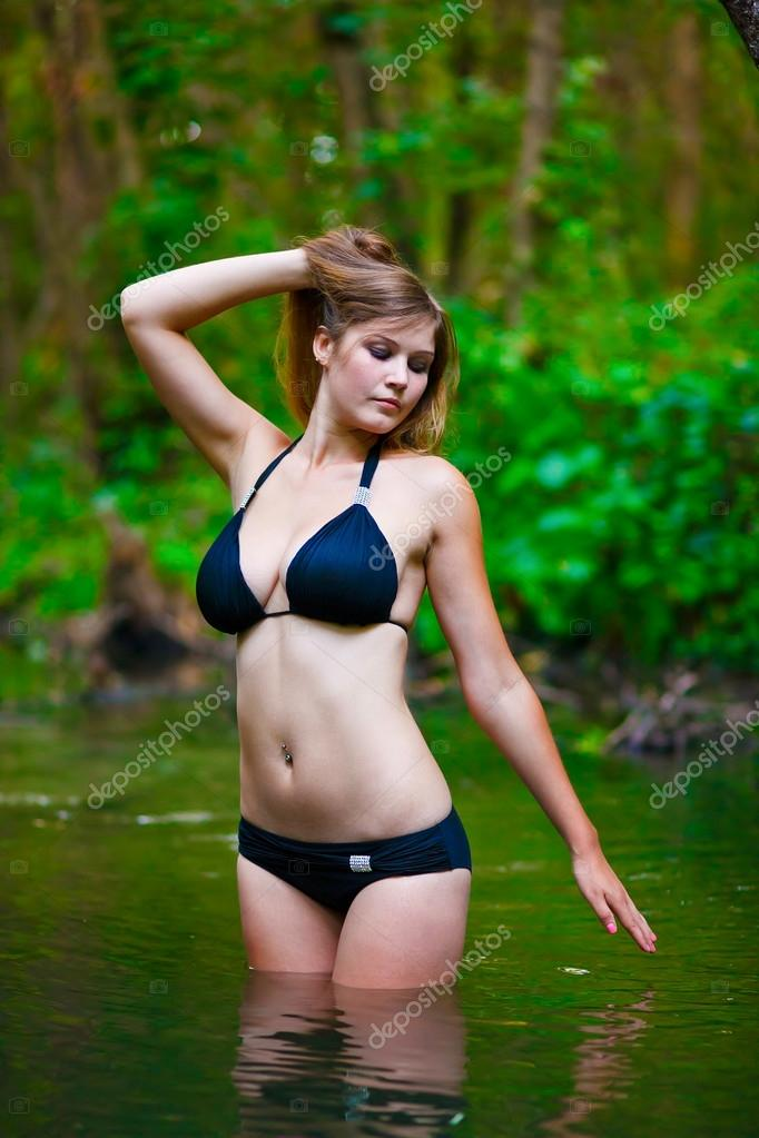 Blonde young woman with big breasts in a black bikini standing o