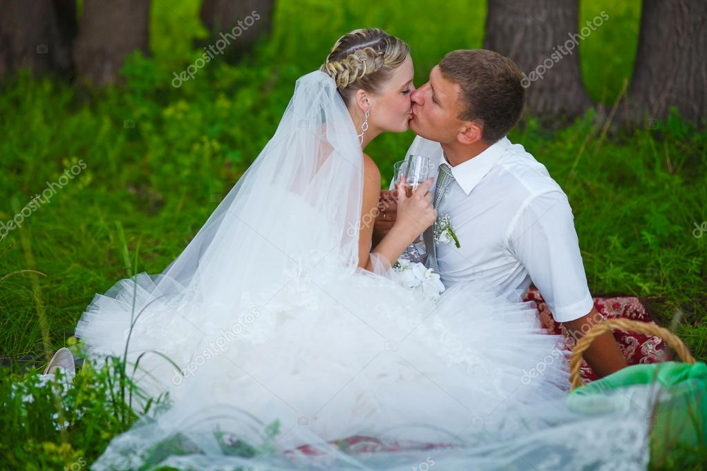 couple kissing at wedding newlyweds picnic in a forest clearing,