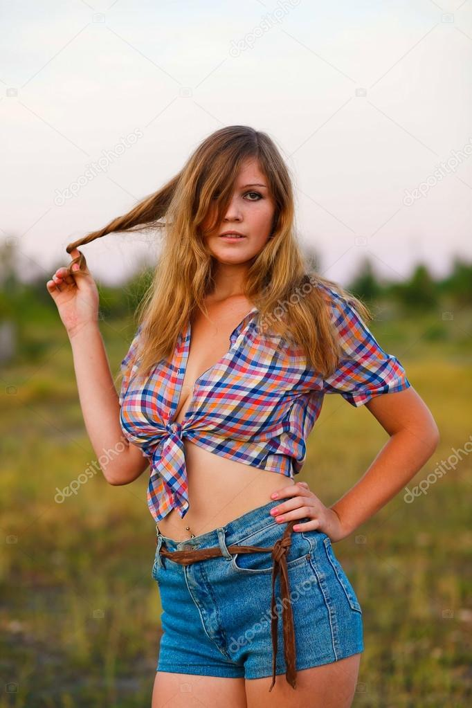 young woman in a plaid shirt, denim shorts at sunset, flowing ha