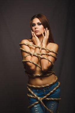 Brunette girl woman bound with rope prisoner in jeans gray backg