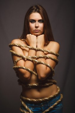 Woman bound rope prisoner in jeans gray background