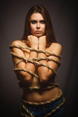Brunette woman bound with rope prisoner