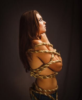 Woman rope bound prisoner hostage stands sideways