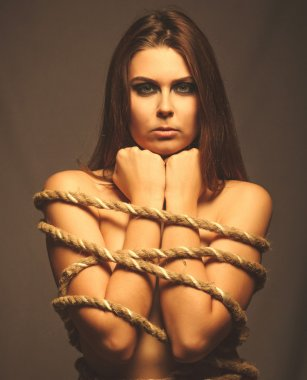 Brunette woman bound with rope prisoner in jeans gray background
