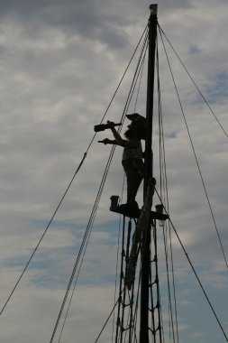 Silhouette of a pirate on the match looking through spyglass