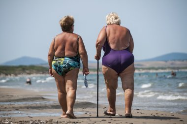 elderly and fat old ladies walk on the beach