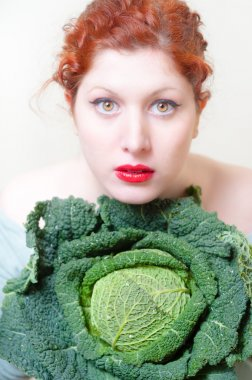 beautiful red hair and lips girl with savoy cabbage