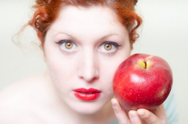 beautiful red hair and lips girl with apple