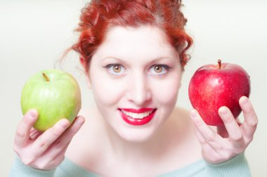 beautiful red hair and lips girl with green and red apple