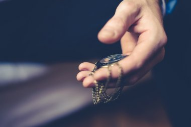 close up of hands with vintage pocket watch
