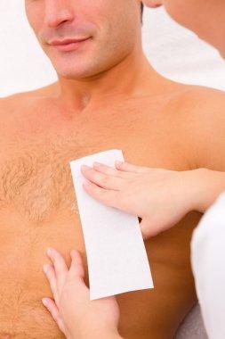 Man waxing his chest hair