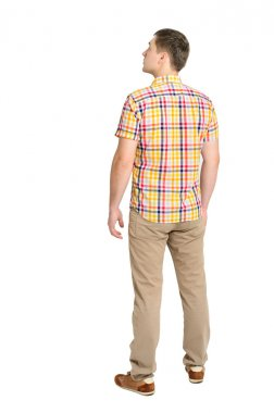 Back view of young man in a plaid shirt and jeans looking