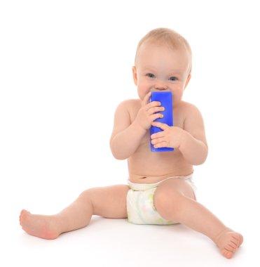 New born infant child eatind blue toy brick