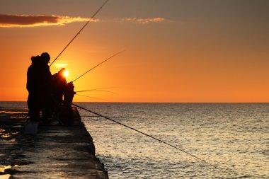 Fishermen at sunrise on the sea