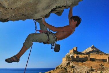 Rock climber on a safety rope on blue sky background