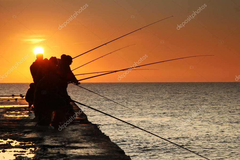 Fishermen on sunrise on the pier