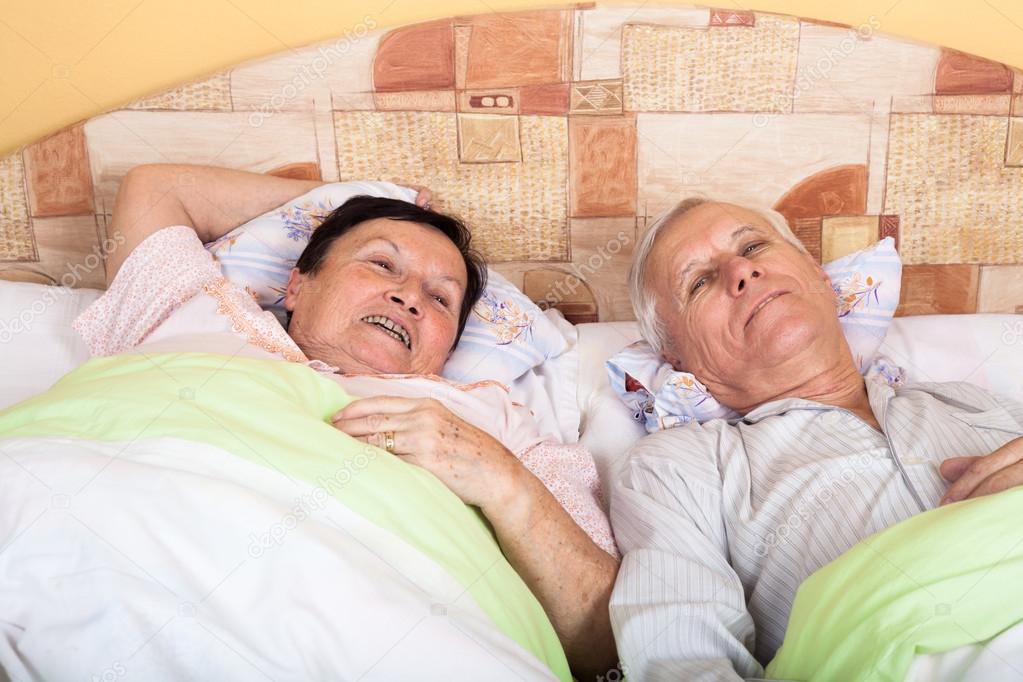 русская пожилая пара лежат в кровати его удивлению