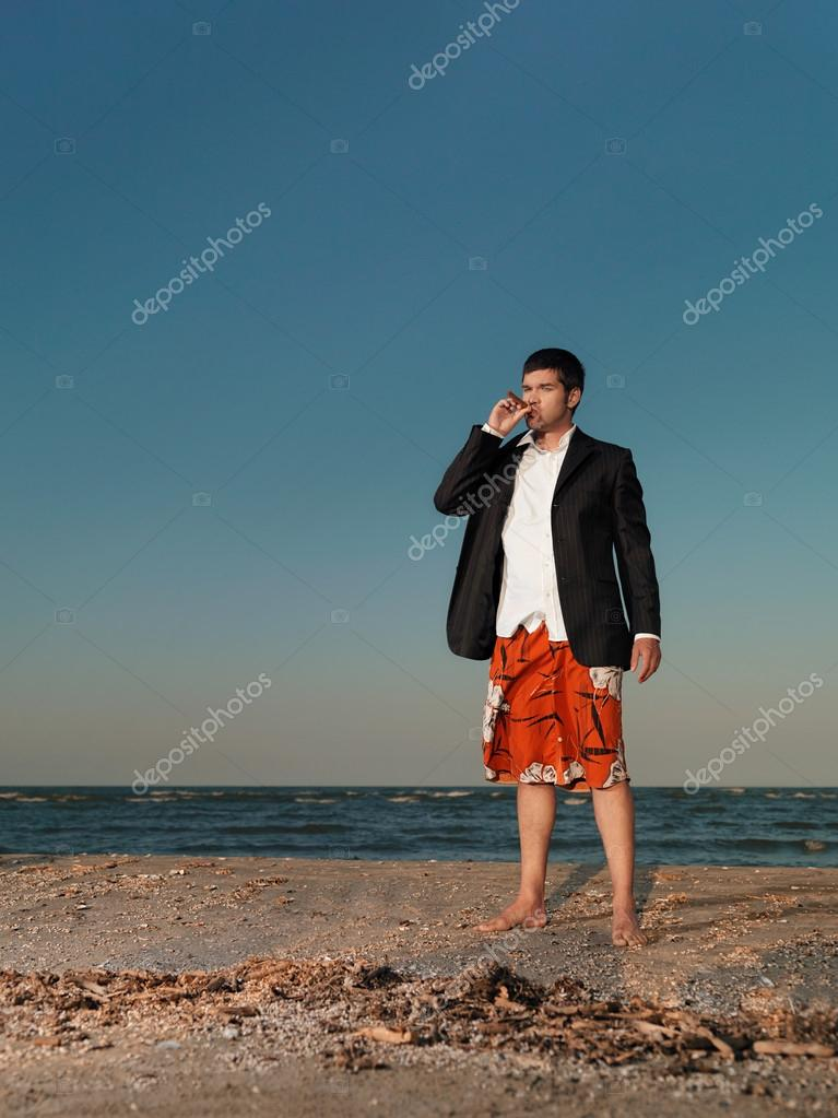 confident businessman smoking cigar on sea shore