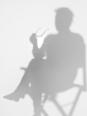 man sitting on director's chair, silhouette