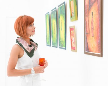 woman admiring paintings in an art gallery